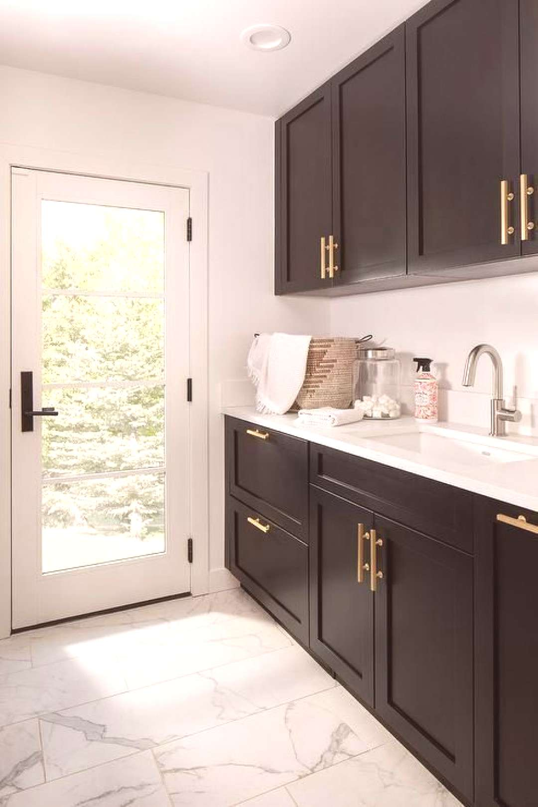 Black shaker laundry room cabinets accented with brushed gold pulls are mounted over a sink with a